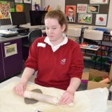 Picture of a pupil rolling clay with a rolling pin