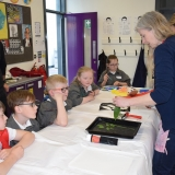Picture of an artist explaining to pupils how to make print art