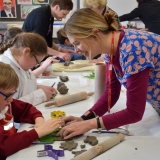 Picture of an artist and pupil working with clay