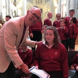 Picture of a pupil receiving an achievement  certificate from Archbishop  Harper