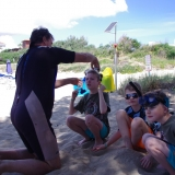 Picture of an instructor helping pupils to get ready to snorkel