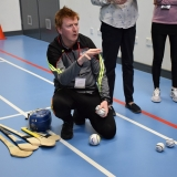 Picture of instructor explaining about hurling and the equipment used in the game