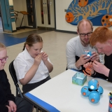 Picture of a teacher with students examining the Dash robot