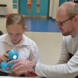 Picture of a teacher and student examining the Dash robot