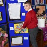 Photograph of pupil standing beside their art work