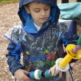 Picture of a pupil playing with a outside tactile hanging toy