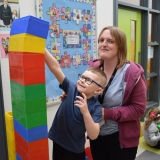 Picture of a staff member helping a pupil build a tower of large coloured blocks