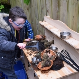 Picture of a pupil playing with a mud kitchen