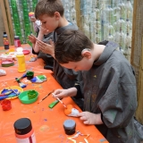 Picture of pupils painting stones in the plastic bottle greenhouse
