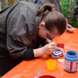 Picture of a pupil painting a stone in the plastic bottle greenhouse