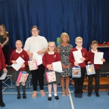 Group photograph of the pupils moving to the secondary department next year after each receiving a gift from the special guest