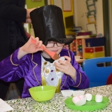 Picture of a pupil filling bun cases with chocolate