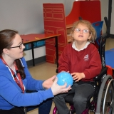 Picture of a classroom assistant and pupil taking part in a sensory story about Willy Wonka's Chocolate Factory