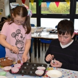 Picture of two pupils filling bun cases with chocolate