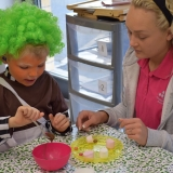 Picture of a classroom assistant with a pupil filling bun cases with chocolate