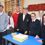 Group picture of the school leavers cutting the celebration cake