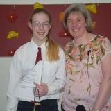 Picture of a school leaver being presented with a gift by  the school  principal