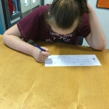 Photograph of a pupil writing a cheque