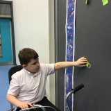 Photograph of a pupil adding their height to a height chart